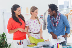 Three fashion designers looking at sketchpad. In a bright creative office Stock Images