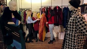 Portrait of three beautiful young women shopping in a clothes shop. stock footage