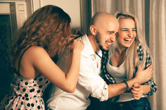 Three fashionable friends at house party laughing. Celebrate, disco, party, nightlife, entertainment, friendship concept Stock Photo