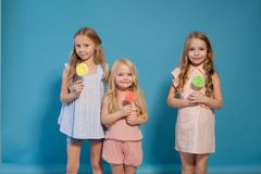 Three girlfriends sisters eat sweet lollipop with sweet chocolate dessert stock photography