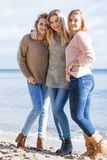 Three fashionable sister on the beach stock images