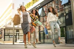 Three fashionable young women strolling with shopping bags. Satisfied women jumping on street. Lifestyle royalty free stock photography