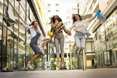 Three fashionable young women strolling with shopping bags. Stock Photography