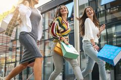 Three fashionable young women strolling with shopping bags Stock Photos