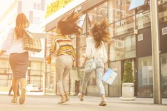 Three fashionable young women strolling with shopping bags. Stock Image