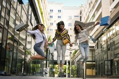 Three fashionable young women strolling with shopping bags. Royalty Free Stock Images