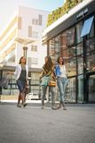 Three fashionable young women strolling with shopping bags. Royalty Free Stock Image