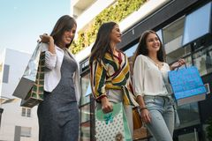 Three fashionable young women strolling with shopping bags. Stock Photo