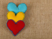 Three felt craft hearts, yellow, red and blue. Felt craft and art, three handmade stitched toy hearts, yellow, red and blue on canvas background, close up stock images