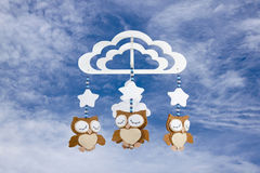 Three Felt Owls on Baby Cot Mobile Against Cloudy Sky Stock Photo