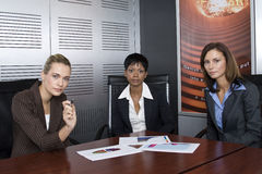Three female business. Multi-racial business team working within an office with a sales graphs Stock Photos