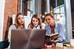 Three female college students studying together using laptop and lecture notes sitting at desk in study room royalty free stock photography