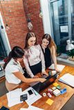 Three female college students working on assignment together using laptop standing at home Stock Photo