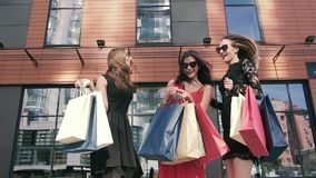 Three female friend meeting outdoors after shopping stock video