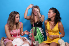 Three female friends among beads and teddy bears. Three girls sitting among their beads and teddy bears Royalty Free Stock Image