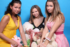 Three female friends with beads and teddy bears Stock Image