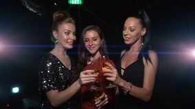 Three female friends cheers and clink glasses with champagne. And have fun on party stock footage