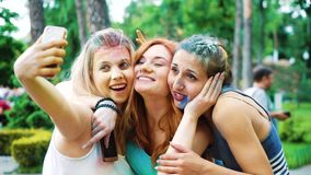 Three female friends in colorful powder make selfie photo after Holi festival. In summer park in slow motion. people spend leisure time together. bonding stock footage