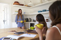 Three female friends drinking coffee together in the kitchen Royalty Free Stock Photography