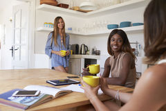 Three female friends drinking coffee together in the kitchen Royalty Free Stock Images