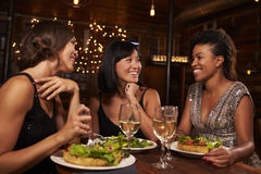 Three female friends eating dinner together at a restaurant Stock Photos