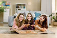 Three female friends eating pizza at the house party while lying on the floor in cozy room royalty free stock photography
