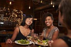 Three female friends enjoying dinner at a restaurant Stock Image