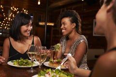 Three female friends enjoying dinner at a restaurant Stock Photos