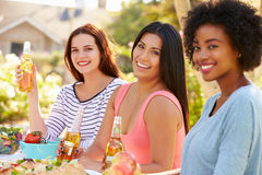Three Female Friends Enjoying Meal At Outdoor Party Stock Photo