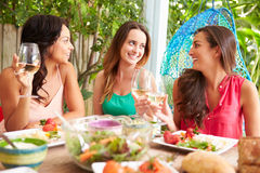 Three Female Friends Enjoying Meal Outdoors At Home Royalty Free Stock Photo