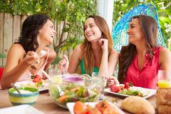 Three Female Friends Enjoying Meal Outdoors At Home Stock Photo