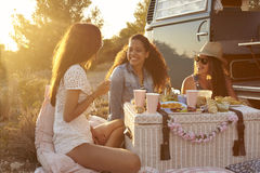 Three female friends enjoying a picnic by their camper van Stock Photo