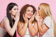 Three female friends gossip and smile telling secrets. Women friendship beautiful ladies. Blonde curly brown and long dark hair Stock Photo
