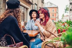 Three female friends having drinks in outdoor cafe. Women chatting and hanging during coffee break royalty free stock photos