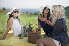 Three female friends having a picnic in nature. Stock Image