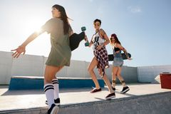Group of women skaters enjoying at skate park. Three female friends running and jumping over skate park ramp. Women skaters enjoying at skate park Royalty Free Stock Photo