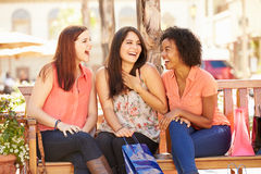 Three Female Friends With Shopping Bags Sitting In Mall Stock Photo