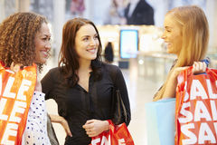 Three Female Friends Shopping In Mall Together Stock Photography