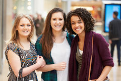 Three Female Friends Shopping In Mall Together Stock Photos