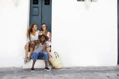 Three female friends sitting in a doorway, Ibiza Stock Image