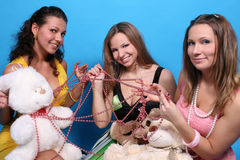Three female friends in studio with beads and toys. Three girls with beads and teddy bears Stock Images