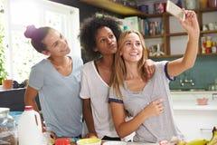 Three Female Friends Taking Selfie Whilst Making Breakfast Stock Image