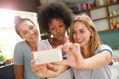 Three Female Friends Taking Selfie Whilst Making Breakfast Royalty Free Stock Images