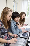 Three female friends using laptop and cell phone Royalty Free Stock Images