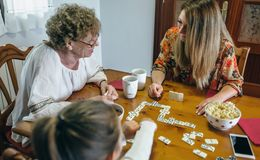Three female generations playing domino Stock Image