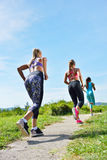 Three Female Joggers running together outdoors Royalty Free Stock Photo