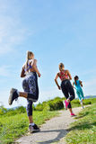 Three Female Joggers running together outdoors Stock Photo