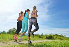Three Female Joggers running together outdoors Stock Images