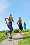 Three Female Joggers running together outdoors Stock Photos