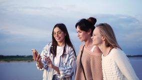 Three female models taking selfie and then looking at photos in the phone while walking.
